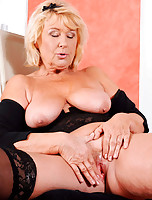 Blonde milf exposes her natural breasts and spreads her slick pussy